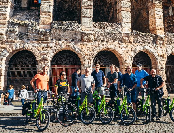 by e-bike in front of Arena of Verona